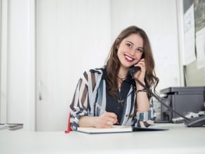 a receptionist on the phone, smiling