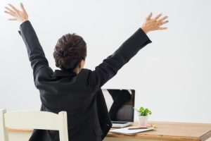 business woman sitting at a table in front of a laptop and small plant with her arms outstretched above her head