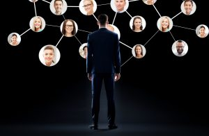 a man in a suit looks at a network of faces