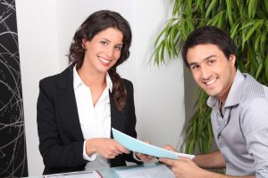 Woman smiling, handing a smiling man documents