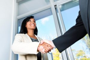 smiling woman shaking hands with a man (mainly arm visible)