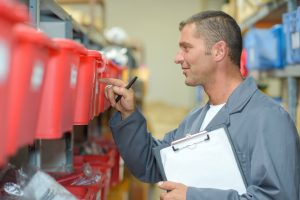 man with a clipboard looking at red bins on a shelf in a warehouse